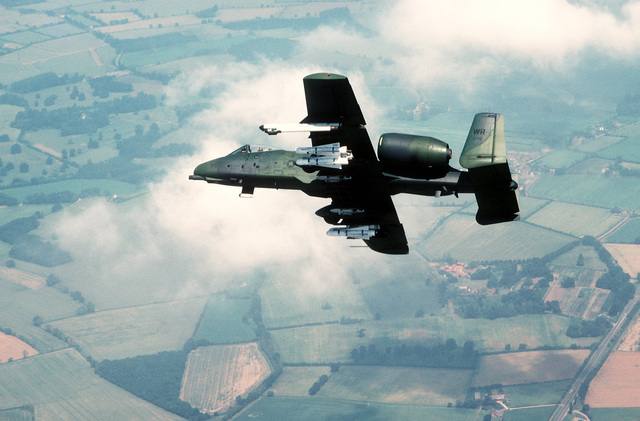 An air-to-air left side view of an A-10 Thunderbolt II aircraft banking to the right. The aircraft, assigned to the 81st Tactical Fighter Wing, is carrying four AGM-65B Maverick scene magnification missiles and an AN/ALQ-119 electronic countermeasures pod