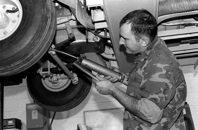 CPL Ray Tippett, an electrician with the ground support equipment section, greases the undercarriage of an NC-8 mobile electric power plant