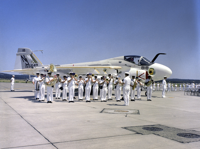 The 13th Naval District Band from Seattle plays for the commander of Medium Attack Tactical Warfare Wing, Pacific change of command ceremony. Behind them is an A-6 Intruder aircraft from Medium Attack Squadron 128 (VA-128)