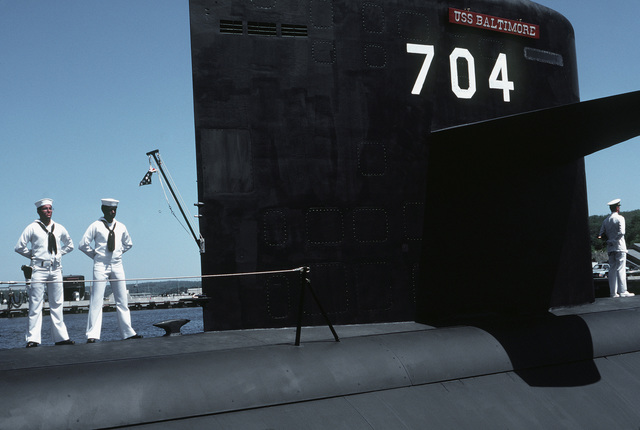 Two crewmen stand at parade rest on the deck of the nuclear-powered attack submarine USS BALTIMORE (SSN-704) during the commissioning ceremony