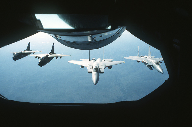 A KC-135A Stratotanker aircraft refuels two A-7 Corsair IIs and one F-15 Eagle during Operation Midnight Sun