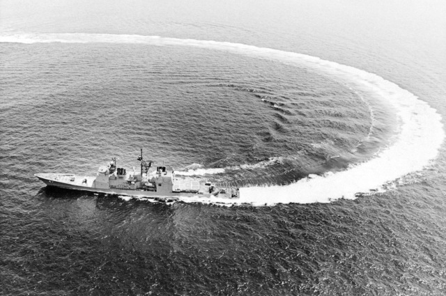 Aerial port beam view of the guided missile cruiser TICONDEROGA (CG-47) performing high speed maneuvers during sea trials