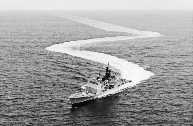 Aerial port beam view of the guided missile cruiser TICONDEROGA (CG-47). The ship is being put through high speed maneuvers during sea trials