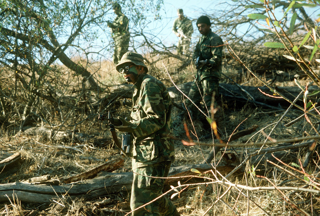 Aggressors in camouflage and armed with M-16 rifles begin their infiltration of a camp's defenses during exercise Prime Beef. The men are from the 4392nd Civil Engineering Squadron