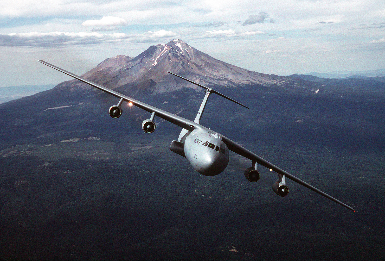 Air to air front view of a USAF's Air Mobility Command, C-141B Starlifter transport aircraft from the 60th Airlift Wing, Travis Air Force Base, California with California's Mt. Shasta in the background. Exact Date Shot Unknown