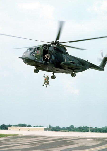 An HH-53C Super Jolly helicopter hovers above the ground as two crewmen rappel from it by a cable during the Boy Scouts of America 1981 National Aviation Explorer Fly-In