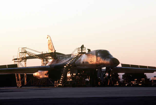 Right front view of a B-1B bomber aircraft, taken in the early morning as technicians begin work