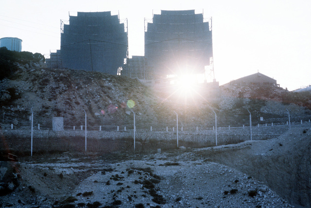 The rising sun outlines a tropo antenna at a communication site above the island of Levkas