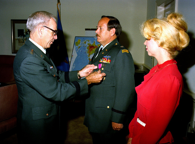 General John W. Vessey, Chairman of the Joint Chiefs of STAFF, presents the Legion of Merit medal to retired Lieutenant Colonel Terry Covington during a ceremony at the Pentagon. Mrs. Covington looks on