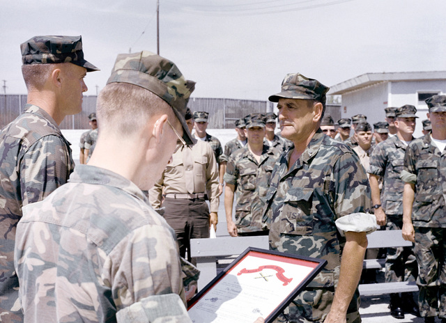 """MGEN James L. Day, commanding general, 1ST Marine Division, Fleet Marine Force, is the recipient of the """"Order of the St. Barbara Award"""". COL Ernest B. Beall, commanding officer of the 11th Marine Regiment, makes the presentation"""