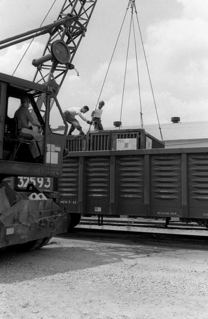 Members of the 1179th Drum Control Unit, Fort Hamilton, New York, guides a shipping container into a railroad car