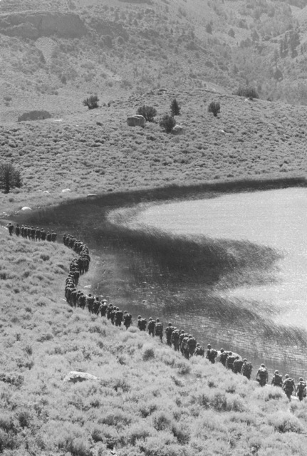 Company B, 1ST Battalion, 9th Marines, march down the side of a lake during their mountain warfare training