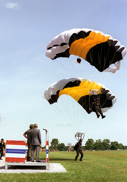 Secretary of the Army John O. Marsh watches as two members of a four-man team land during a performance by the Screaming Eagles Sports Parachute Club at the Division Review