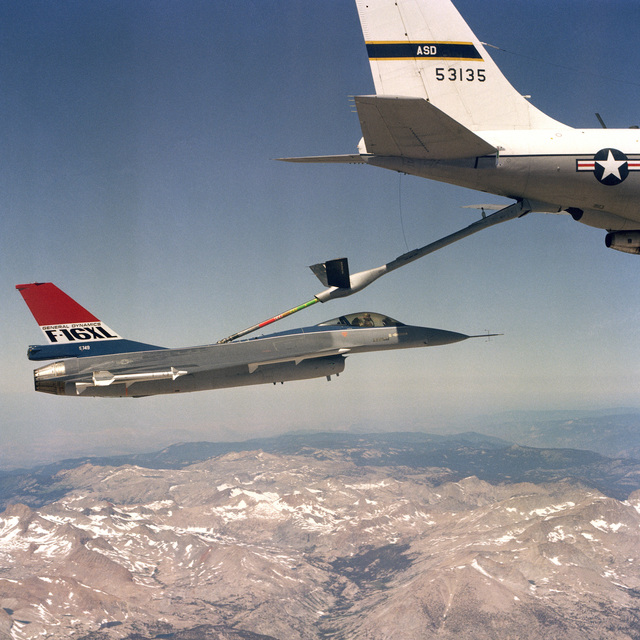 An air to air right side view of an F-16XL aircraft are being refueled in flight by a KC-135 Stratotanker. The F-16 is armed with four fuselage mounted AIM-7 Sparrow missiles