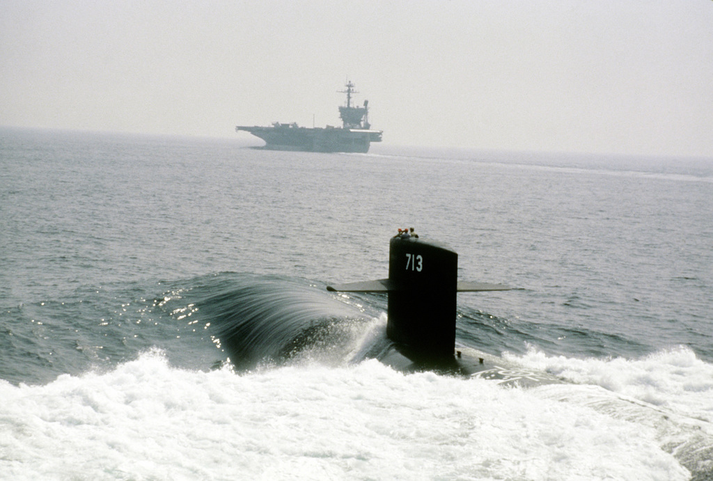A port quarter view of the view of the nuclear-powered attack submarine HOUSTON (SSN-713), foreground, and the aircraft carrier USS JOHN F. KENNEDY (CV-67), background, departing Hampton Roads for a patrol