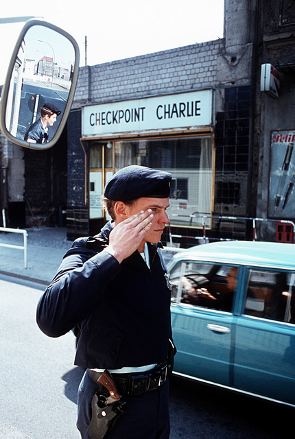 A1C David Smith, a security policeman, salutes a passing vehicle at Checkpoint Charlie, the allied entry point into East Berlin
