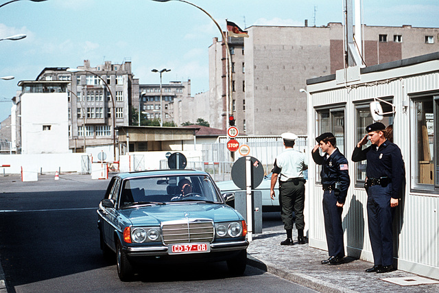 A1C David Smith (right) and Steven Freeman, both security policemen from the 7350th Air Base Group, salute a passing vehicle at Checkpoint Charlie, the allied entry point into East Berlin