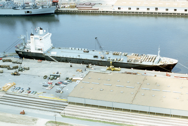 An aerial starboard beam view of the civilian transport ship CYGNUS (T-AK-113) being loaded with supplies and equipment for Exercise Reforger in Europe. The CYGNUS is being leased by the Military Sealift Command to assist in the transport operation