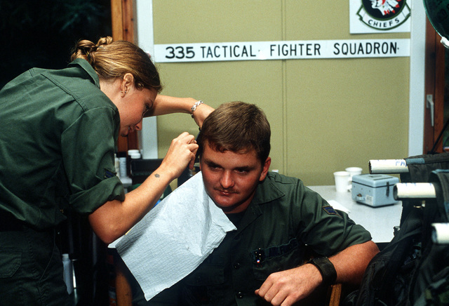 A1C Lisa Hicks cuts A1C Cory Livesay's hair in the life support section during Exercise Reforger-Coronet Musket. The airmen are assigned to the 335th Tactical Fighter Squadron, Seymour Johnson Air Force Base, North Carolina