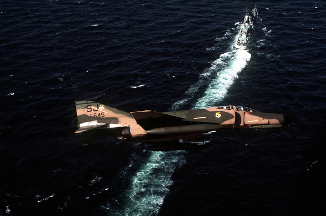 Right side view of an F-4E Phantom II aircraft from the 335th Tactical Fighter Squadron, Seymour Johnson Air Force Base, N.C., in flight during Reforger-Coronet Musket. The Danish frigate Peder Skram (F-352) is underway in the background