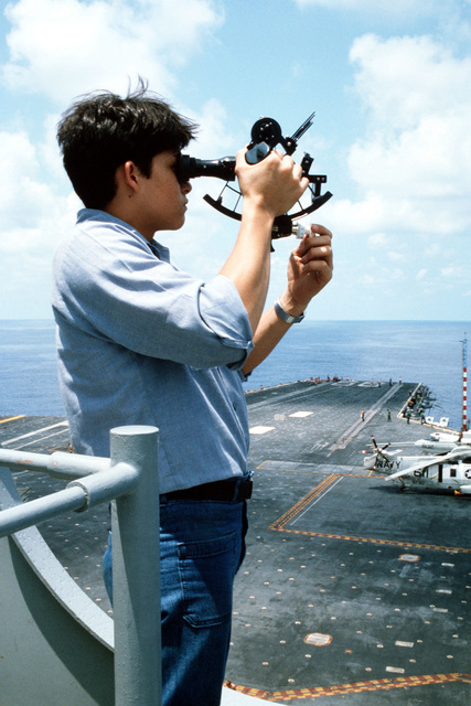 A crewman uses a sextant (a navigational device) to plot a course for the aircraft carrier USS AMERICA (CV 66)