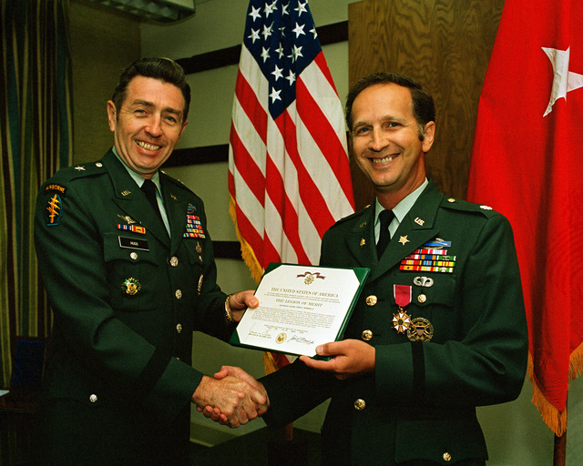 BGEN Victor J. Hugo, left director, Management Directorate, Office of the CHIEF of STAFF, presents the Legion of Merit to LCOL Joseph J. Momorella, a research and evaluation staff officer within the Management Directorate. The ceremony is taking place at the Pentagon