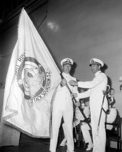 CDR Bruce V. Woods accepts the squadron banner from outgoing commanding officer, CDR David T. Wagner, during the change of command ceremony for Attack Squadron 52 (VA-52)