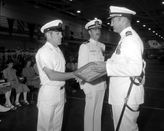 CDR Bruce V. Woods, new commander of Attack Squadron 52 (VA-52), presents a chief with a squadron plaque upon his retirement