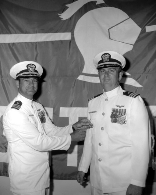 CDR David T. Wagner (left) pins the command badge on the new commanding officer, CDR Bruce V. Woods, during the change of command ceremony for Attack Squadron 52 (VA-52)