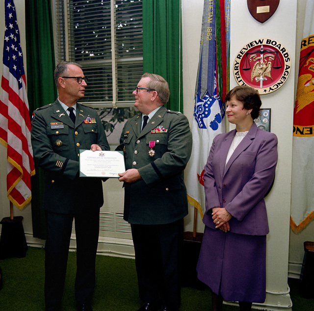 COL J.W. Rowe, deputy director, Army Council of Review Boards, presents the Legion of Merit to LCOL John R. Wallace, at a ceremony held at the Pentagon. Looking on is Wallace's wife, Monica