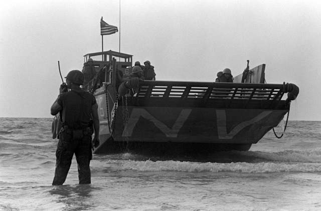 A beachmaster speaks on his two-way radio as preparations are made to lower the ramp of a utility landing craft during landing operations. U.S. Marines have been assigned to Lebanon as part of a multinational peacekeeping force following a confrontation between Israeli forces and the Palestine Liberation Organization
