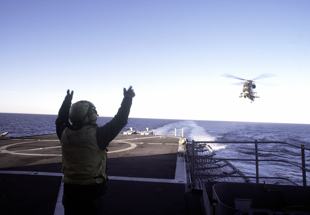 A flight deck crewman signals an SH-2F Seasprite light airborne multi-purpose system (LAMPS) helicopter upon landing on a Unitas XXI ship. The helicopter is attached to Light Helicopter Anti-submarine Squadron 34 (HAL-34)