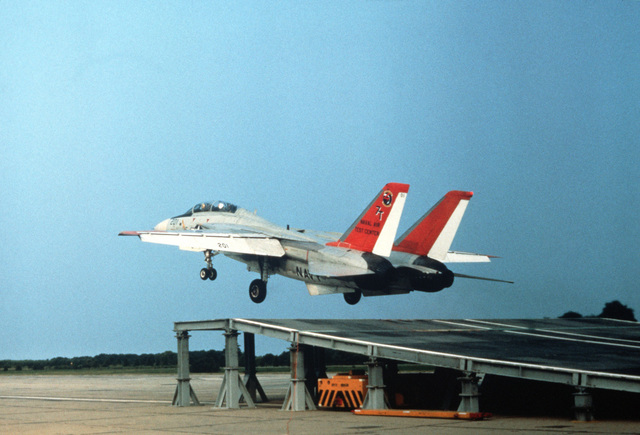 "A left side view of an F-14A Tomcat aircraft taking off from a ramp, raised nine degrees, during ""ski jump"" feasibility tests"