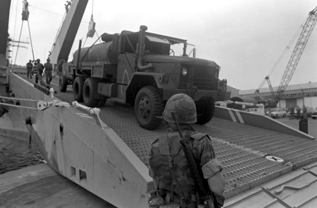 A Marine vehicle rolls down the bow ramp of the tank landing ship USS SAGINAW (LST-1188). The vehicles will be used by Marines assigned to Lebanon as part of a multinational peacekeeping force after a confrontation between Israeli forces and the Palestine Liberation Organization