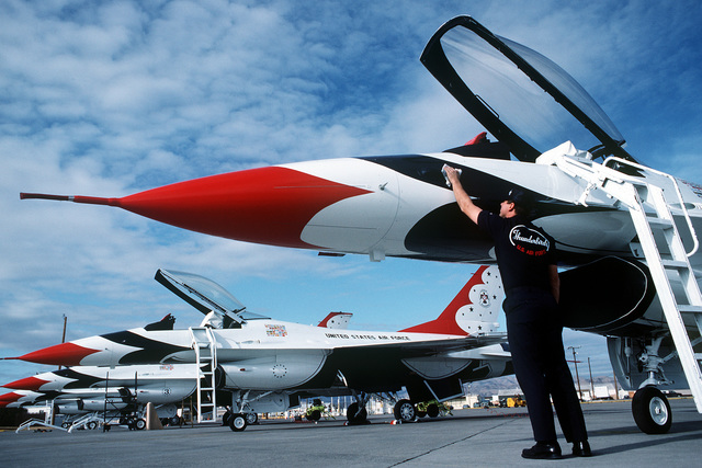 A member of the Air Force Thunderbirds Air Demonstration Squadron maintenance crew polishes one of the team's six F-16 Fighting Falcon