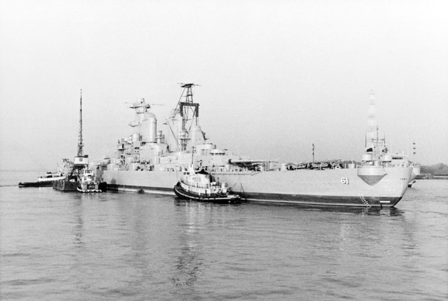 A port quarter view of tugs pushing the battleship USS IOWA (BB 61) into Avondale Shipyards Inc. for modernization and reactivation