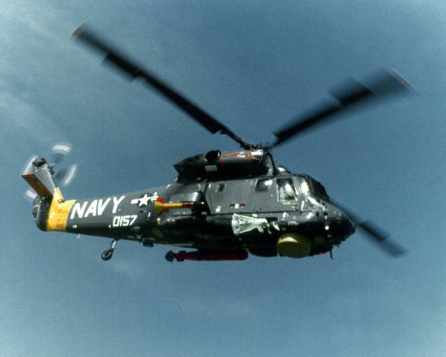 A right side air-to-air view of an SH-2 Seasprite Mark 1 Light Airborne Multi-Purpose System (LAMPS) helicopter. Note the surface search radar, ASQ-81 Magnetic Anomaly Detection (MAD) gear mounted on the right side and the anti-submarine warfare torpedo on the left