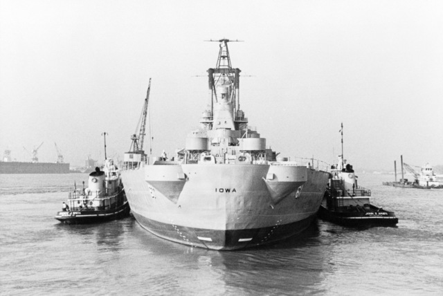 A stern view of tugs pushing the battleship USS IOWA (BB 61) into Avondale Shipyards Inc. for modernization and reactivation