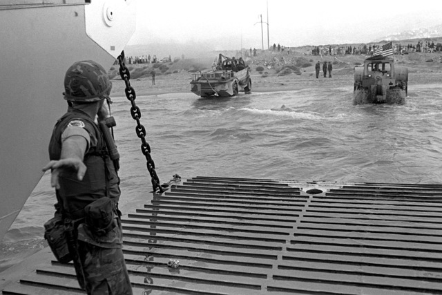 A U.S. Marine beachmaster directs the offloading of amphibious vehicles from the amphibious transport dock USS NASHVILLE (LPD-13). U.S. Marines have been assigned to Lebanon as part of a multinational peacekeeping force following a confrontation between Israeli forces and the Palestine Liberation Organization
