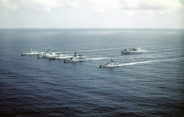 Aerial port bow view of the ships comprising the Standing Naval Force Atlantic underway. The ships are from left to right: HMS DANAE (F-47), HMCS IROQUOIS (DDH-280), HNLMS VAN NES (F-805), USS SELLERS (DDG-11) and FGS AUGSBURG (F-222). Following the ships is the HMCS PROTECTEUR (AOR-509)
