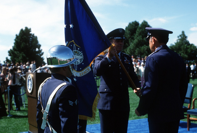 Air Force Vice-CHIEF of STAFF GEN Jerome E. O'Malley presents the new Space Command flag to GEN James V. Hartinger during the dedication ceremony for the Space Command