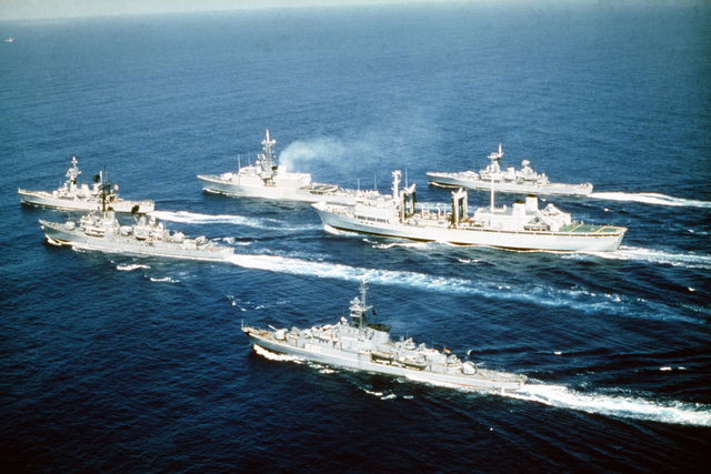 An aerial port beam view of the ships comprising the Standing Naval Force Atlantic underway. The ships are, from top to bottom: HMS DANAE (F-47), HMCS IROQUOIS (DDH-280), HMCS PROTECTEUR (AOR-509), HNLMS VAN NES (F-805), USS SELLERS (DDG-11) and FGS AUGSBURG (F-222)
