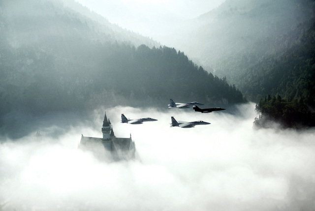 An air-to-air formation of four fighters participating in REFORGER '82 fly over the cloud shrouded Neuschwanstein Castle on the German/Austrian border. The flight of three F-15 Eagles from Eglin Air Force Base, Florida is lead by a German Air Force F-104 Starfighter. Exact Date Shot Unknown