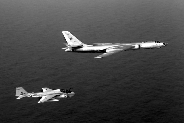 An air-to-air right side view of a Medium Attack Squadron 95 (VA-95) A-6E Intruder aircraft, assigned to the nuclear-powered aircraft carrier USS ENTERPRISE (CVN 65), escorting a Soviet Tu-16 Badger aircraft