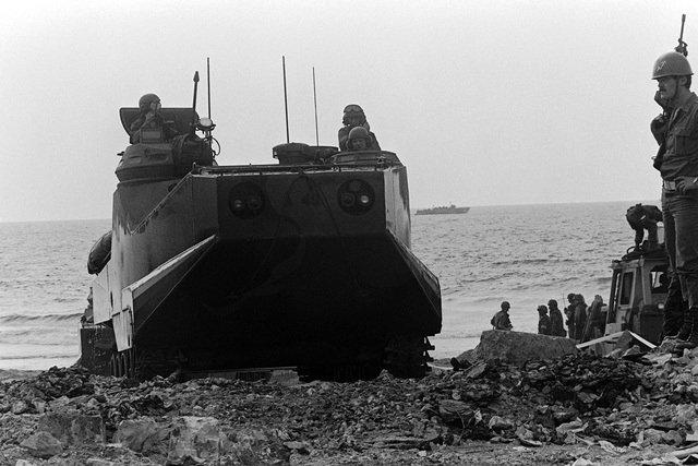 An LVTP-7 tracked landing vehicle comes ashore as U.S. Marines disembark from a tank landing ship (LST). U.S. Marines have been assigned to Lebanon as part of a multinational peacekeeping force after a confrontation between Israeli forces and the Palestine Liberation Organization