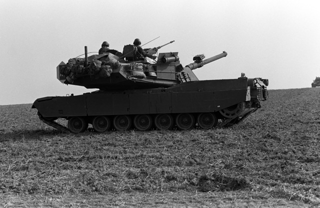 "An M-1 Abrams tank assigned to the 2nd Battalion, 64th Armor, 3rd Infantry Division, Schweinfurt, West Germany, moves out during Carbine Fortress, part of Exercise REFORGER '82. The tank is part of the ""Friendly Forces"", on the defensive"