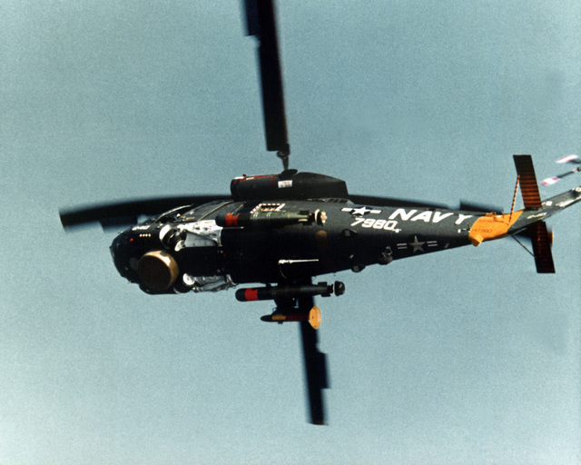 Bottom view of an SH-2 Seasprite Mark 1 Light Airborne Multi-Purpose System (LAMPS) helicopter in flight. Note the surface search radar, ASQ-81 Magnetic Anomaly Detection (MAD) and anti-submarine warfare torpedoes