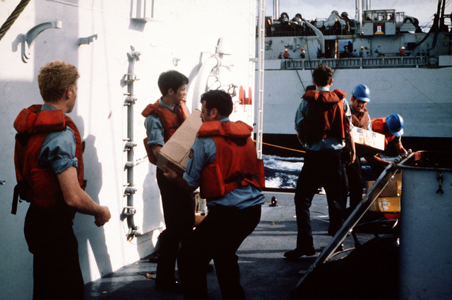 Canadian sailors aboard the HMCS IROQUOIS (DDG-280) transfer crates from the HMCS PROTECTEUR (AOR-409) to storage compartments during underway replenishment operations