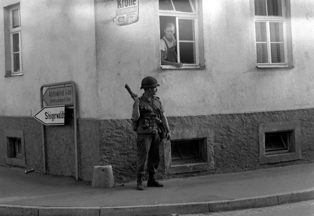 CPL Patrick Williams, stands at the corner of a building with his weapon (type unknown), during Exercise Reforger-Carbine Fortress