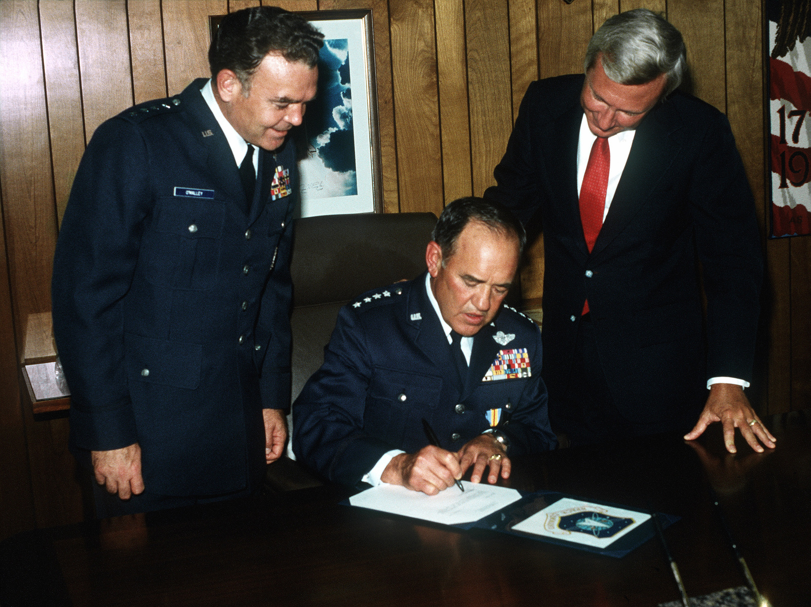 GEN James V. Hartinger signs his first special order as commander of the recently formed Space Command. Under Secretary of the Air Force Edward C. Aldridge Jr. and Air Force Vice-CHIEF of STAFF GEN Jerome E. O'Malley look on